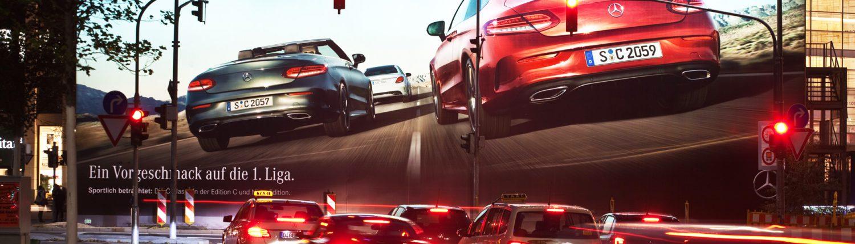Nachts, beleuchtete Mercedes-Werbung an einer Ampel, Fahrzeuge warten