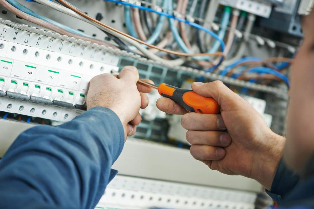 Elektro-Techniker an einem Schaltkasten, Schraubendreher in seiner rechten Hand