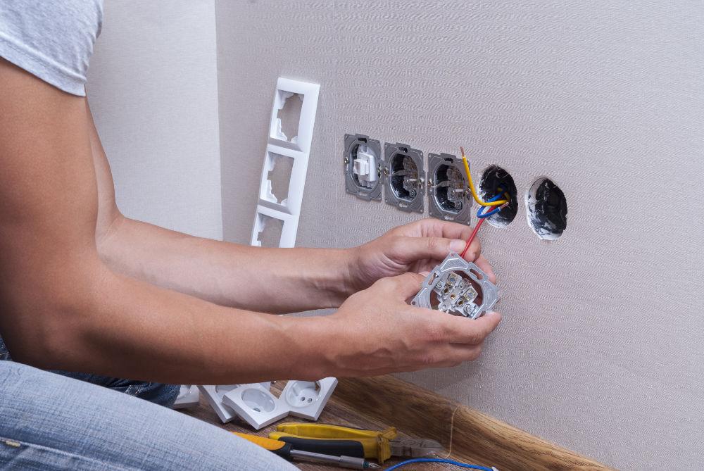 Elektro-Techniker bei der Montage einer Wandsteckdose, drei Kabel offen